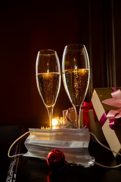 Champagne glasses on table near presents and face mask