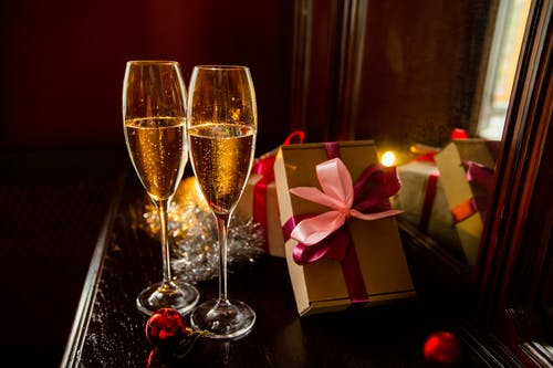 Composition of glasses of champagne placed on table near presents and festive decorations during Christmas celebration