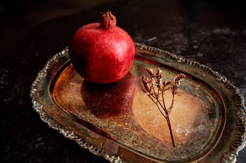 From above sweet ripe pomegranate and thin plant twig on metal ornamental tray placed on dark table