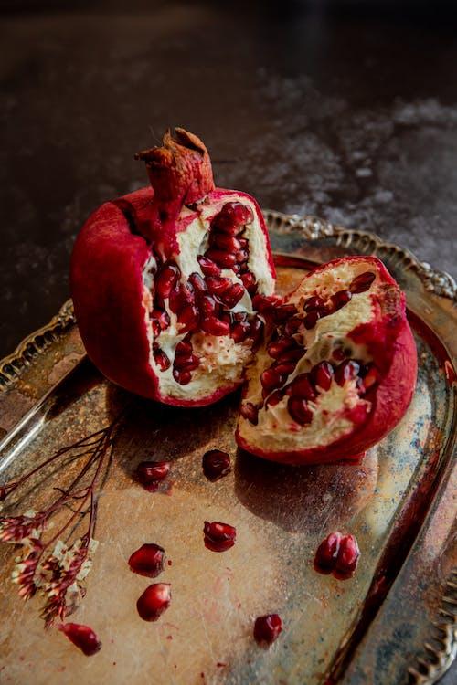 Cut tasty pomegranate on steel tray