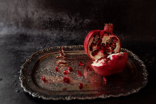 Composition of ripe cut pomegranate placed on metal tray near seeds and thin plant twig