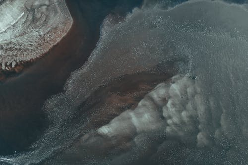 Abstract background top view of rippled dark ocean water surface with foamy waves in daylight
