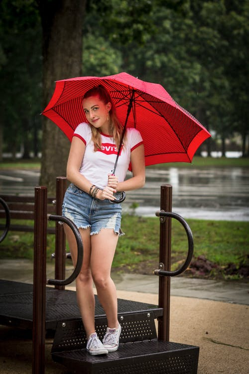 Woman in White T-shirt and Blue Denim Shorts Holding Red Umbrella