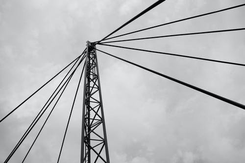 Suspension bridge tower with cables against cloudy sky
