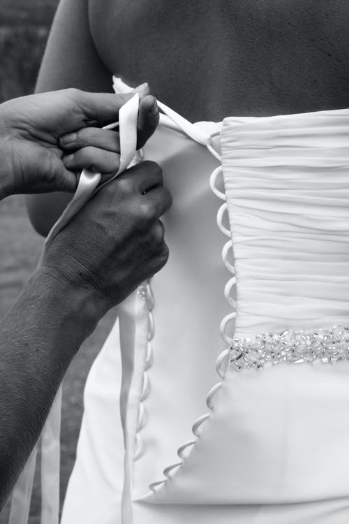 Black and white crop anonymous bridesmaid tying laces on elegant bride wedding dress before ceremony