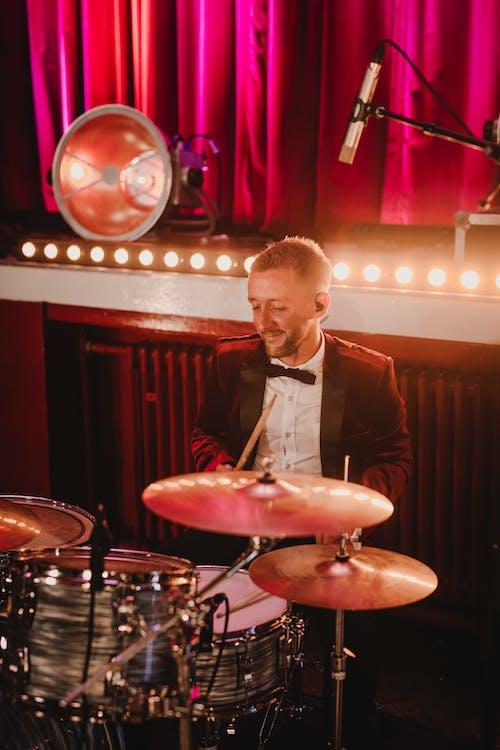Man in Black Suit Jacket Standing Near Drum Set