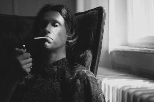 Thoughtful man lighting cigarette in room