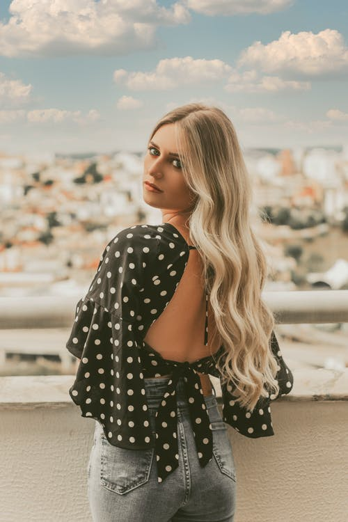 Back view of slim young female in casual outfit with long blond hair standing on balcony and looking at camera over shoulder