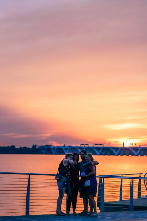 Man and Woman Sitting on Bench Near Body of Water during Sunset