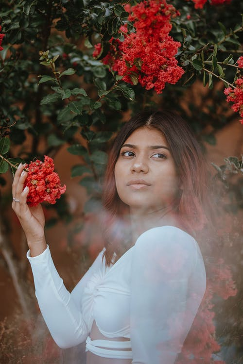 Woman in White Long Sleeve Shirt Holding Red Flowers