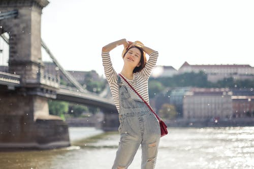 Positive woman standing near river in city