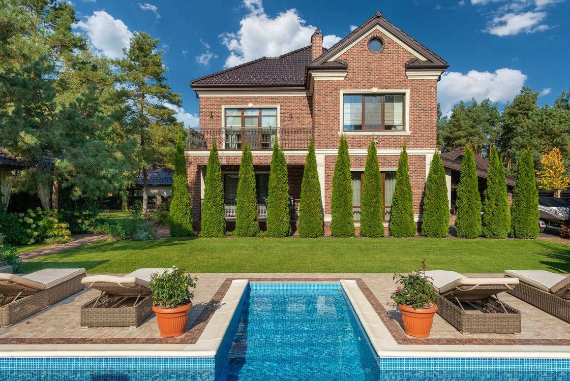 Facade of brick dwell villa with green bushes on lawn and sunbeds near swimming pool