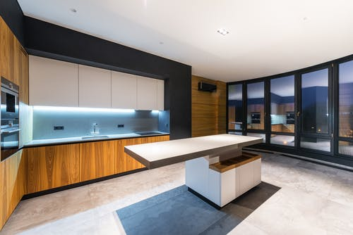 Interior of contemporary kitchen with huge windows against table and bright illumination in cooking zone