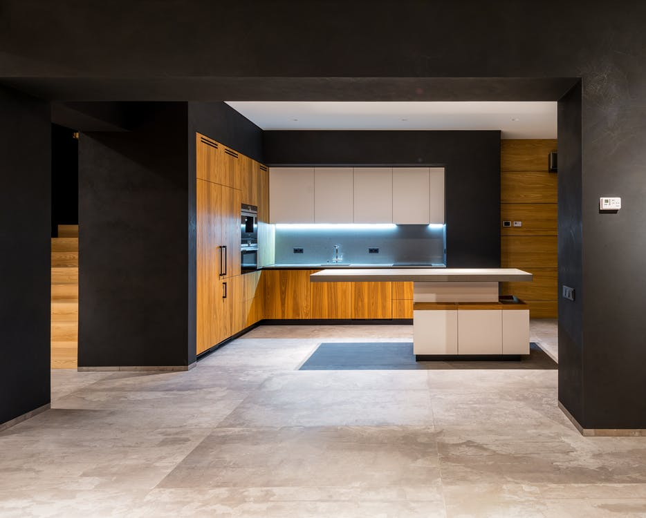 Interior of modern cottage with marble floor and spacious kitchen with wooden furniture and floating tabletop