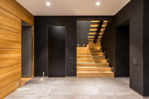 Interior of empty hallway with dark door in wall and stylish wooden stairs