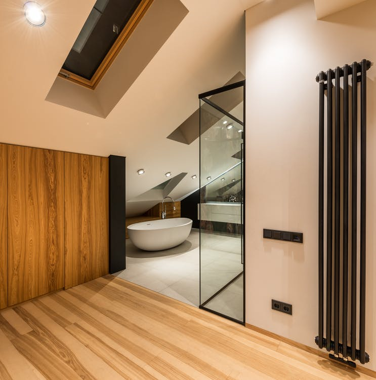 Interior of modern bathroom with wooden elements near entrance and bright illumination over bathtub