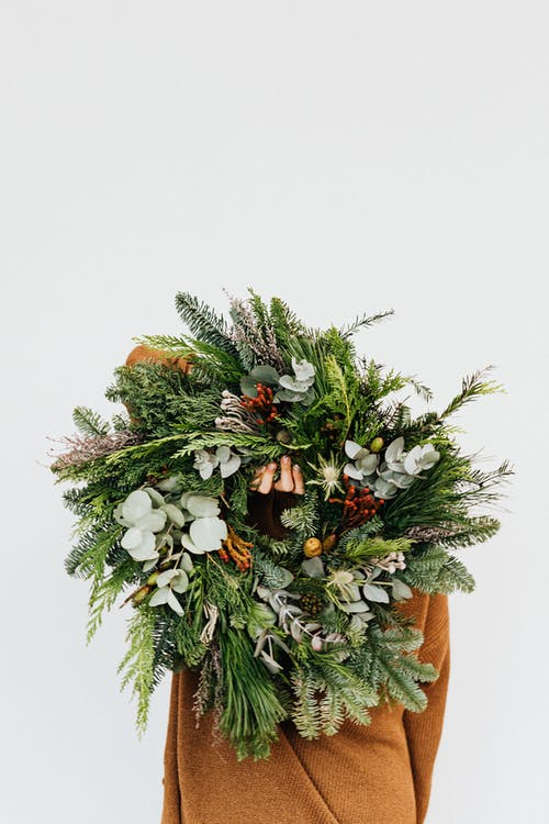 Person Holding a Christmas Wreath Decoration