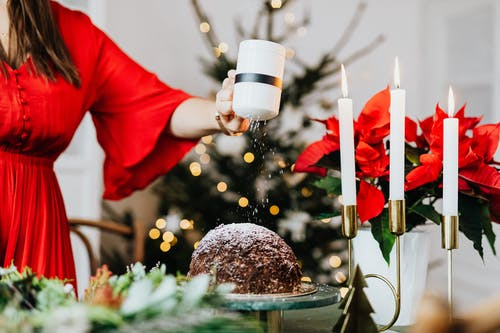 Woman Decorating a Chocolate Cake with Powdered Sugar