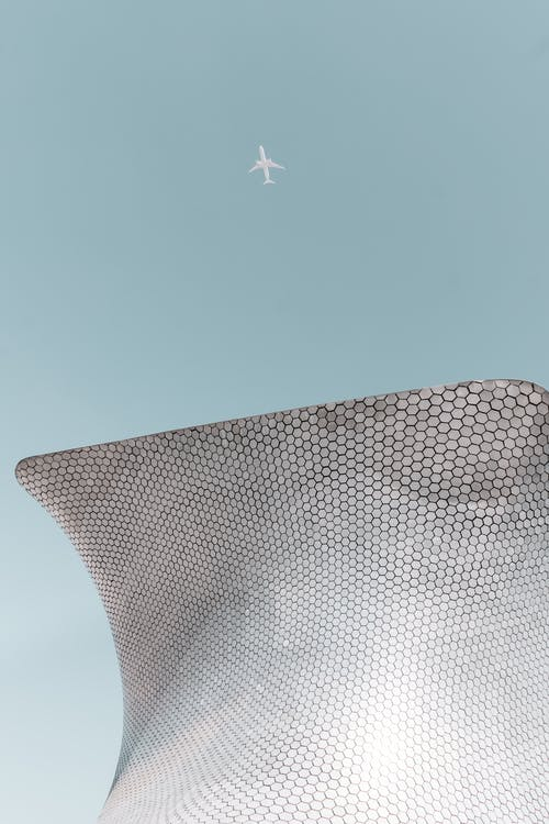 From below shot of passenger airplane flying in cloudless blue sky over modern building of unusual architecture