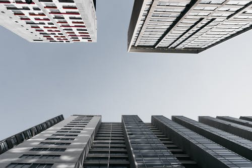 From below of contemporary multistory buildings with geometric shapes located in downtown of modern city