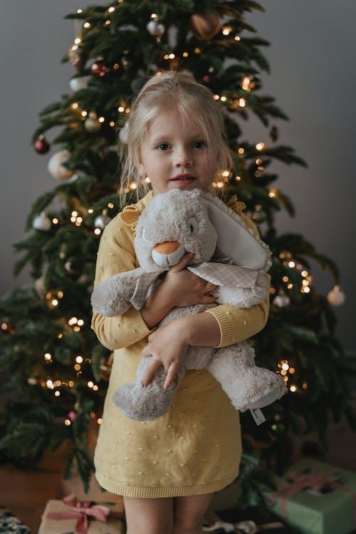 Girl in White Long Sleeve Shirt Hugging Bear Plush Toy