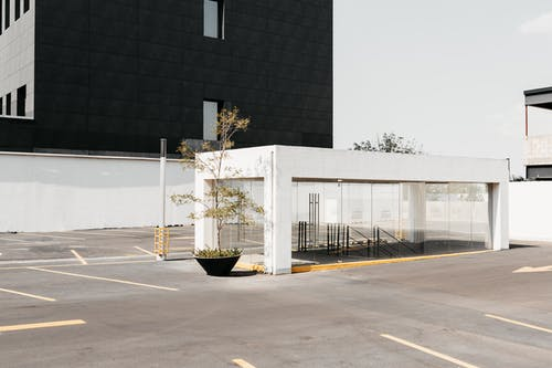 Empty parking with entrance to underpass near modern residential building in sunny day