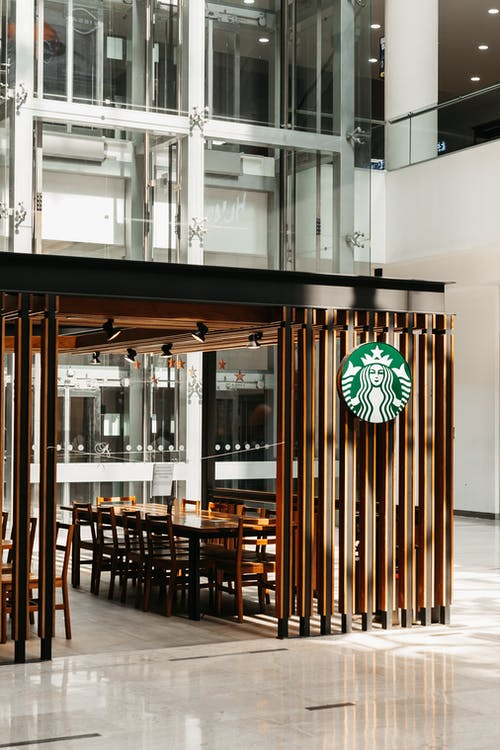 Empty famous coffee shop with wooden tables and logo in modern shopping mall
