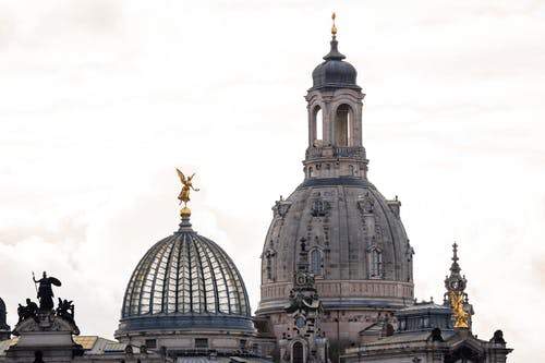 From below facade of ancient baroque styled Frauenkirche church with bell tower and building of Academy of Fine Arts with glass dome under cloudy sky in Dresden