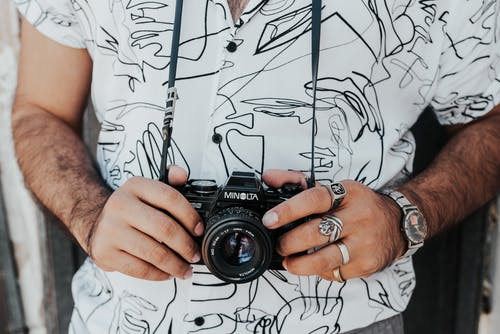 Crop anonymous male photographer in casual wear with accessories standing with professional photo camera