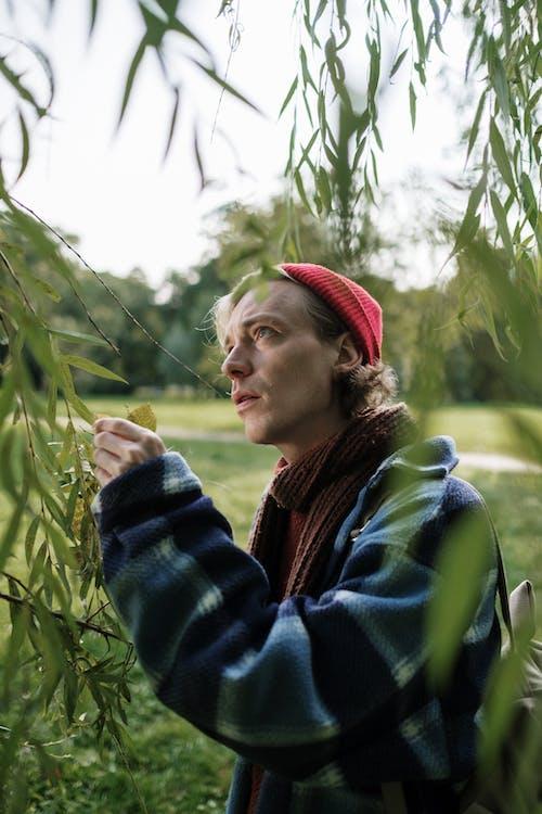 青と緑のジャケットと緑の植物の近くに立っている赤いニット帽の女性