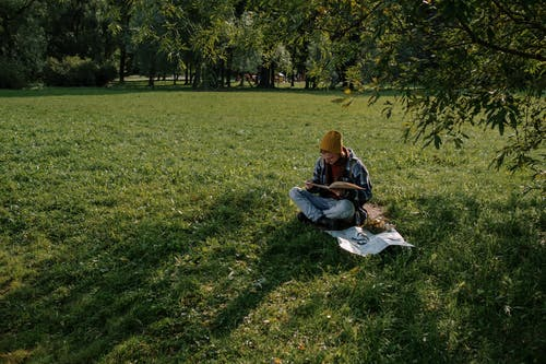 A Man Sitting on Grass Field while Reading a Book for Information