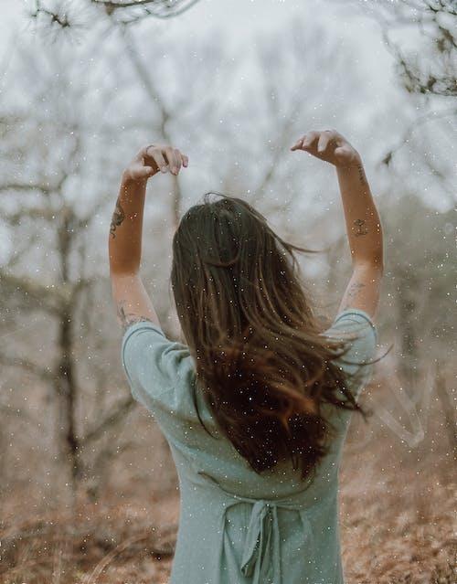 Woman in Teal Long Sleeve Shirt Raising Her Hands