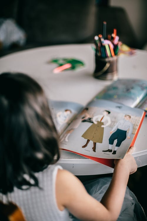Back view of unrecognizable little girl sitting at table and turning pages of book with pictures