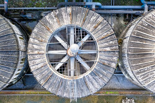 Drone top view of big shabby old metal ventilation fans on factory among pipes