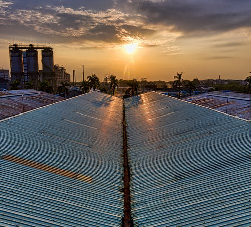 Metal rusty gray roof of construction in industrial area on modern factory in tropical country on sunset against cloudy sky