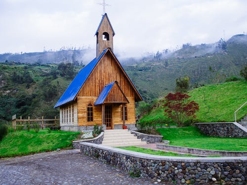 Brown and Black Concrete Church Near Green Trees