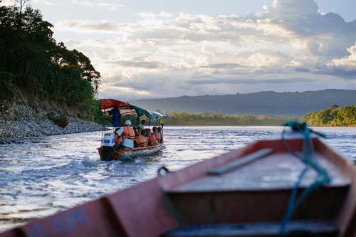 People Riding on Boat on Body of Water