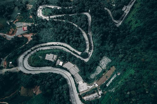 Winding rural roadway through green hilly countryside