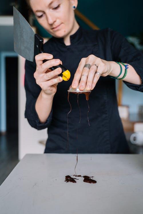 Person in Black Long Sleeve Shirt Holding Orange Round Fruit