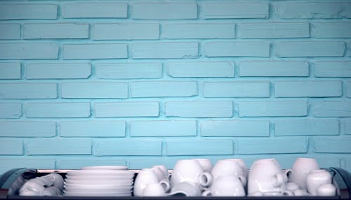 White clean ceramic plates and cups placed on table against blue brick wall after washing in kitchen