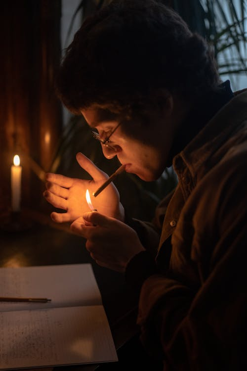 Man in Brown Dress Shirt Lighting a Candle