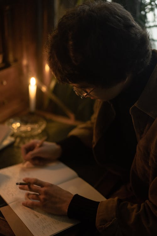 Woman in Brown Coat Writing on White Paper
