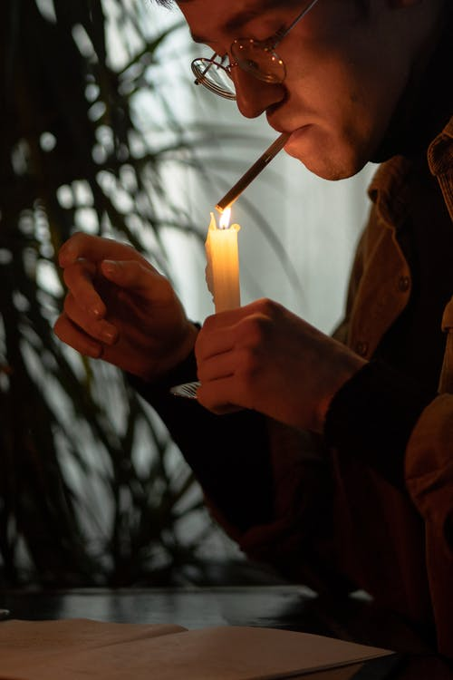 Woman in Brown Coat Holding Lighted Candle