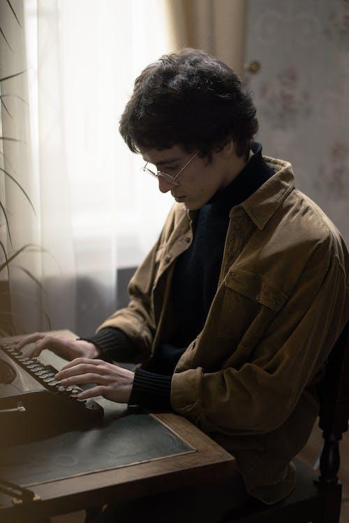 Man in Brown Jacket Using Laptop Computer