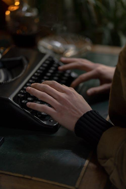 Person Using Black Typewriter on Table