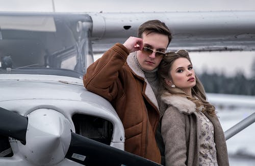 Young couple in trendy warm wear standing close near turboprop airplane on winter airfield and looking at camera