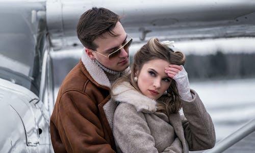 Romantic couple hugging near jet on winter airfield