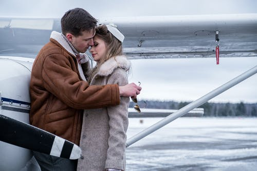 Loving couple bonding near propeller jet on snowy airfield