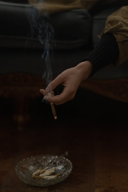 Person Holding Cigarette Stick With Fire