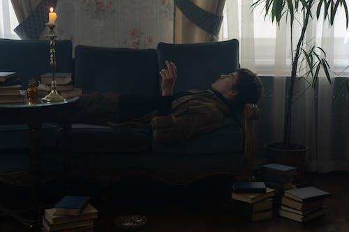 Woman in Black Shirt Lying on Sofa